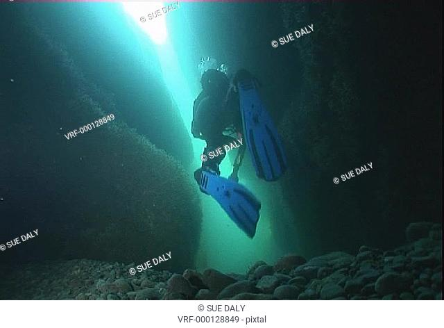 Low angle view diver exploring area of cavesChannel Islands, UKnew. Channel Islands, UK