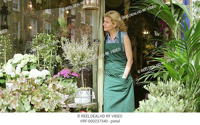 A Florist stands in the doorway of her shop proudly admiring her flowers and business