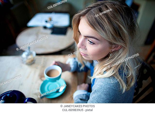Young woman sitting in cafe, holding tea cup, thoughtful expression on face