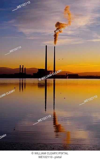 Sunset over Dublin Bay, Ireland  In the centre is Poolbeg Power Station, with smoke billowing from its right cooling tower
