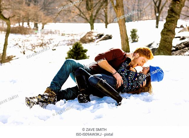 Romantic young couple lying down in snowy Central Park, New York, USA