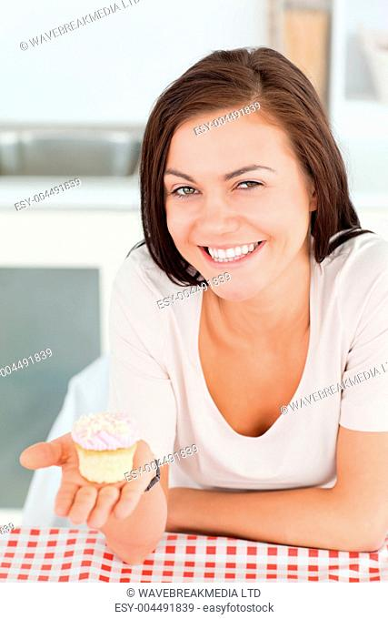 Laughing brunette showing a cupcake