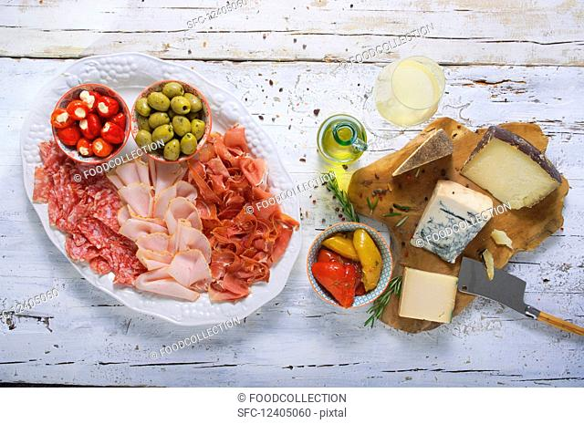 Cheese and sausage platter with olives, stuffed vegetables and white wine