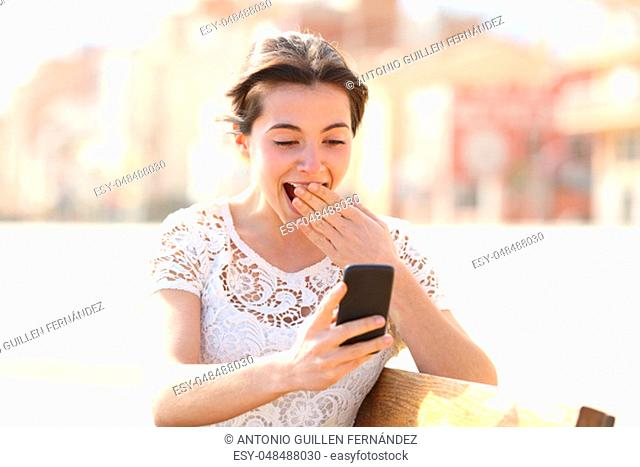 Surprised woman reading amazing news on a smart phone sitting on a bench in a park