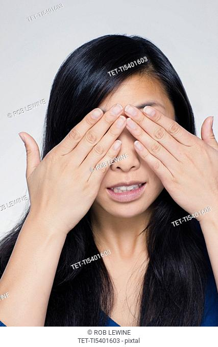 Studio portrait of young woman covering eyes