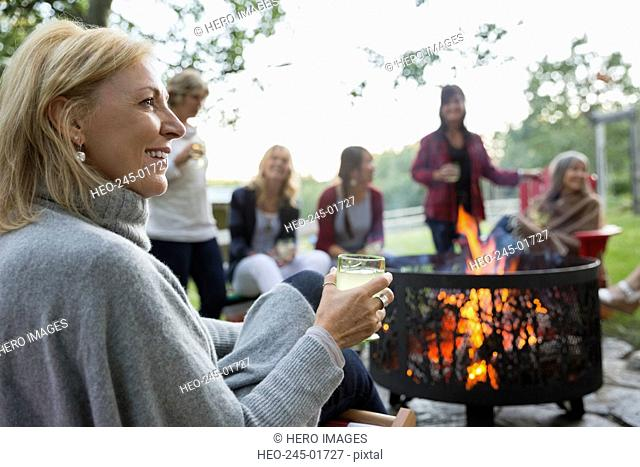 Women relaxing and drinking around fire in backyard