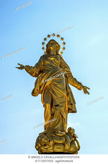 The statue of the Madonna (La Madonnina) on the top of the highest spire of the Milan Cathedral, Milan, Lombard, Italy