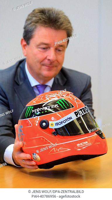 ATTENTIONEMBARGOFORONLINE- 04 JULY2013 - 10:00 AM) Lord Mayor of Magdeburg Lutz Truemper holds the Formula One helmet of MichaelSchuhmacher made by...