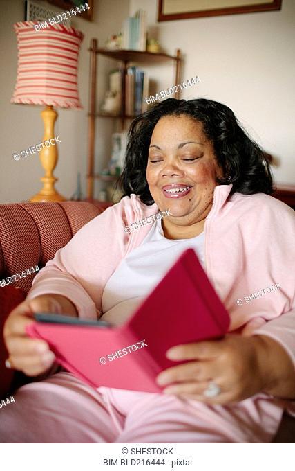 Woman using digital tablet in living room