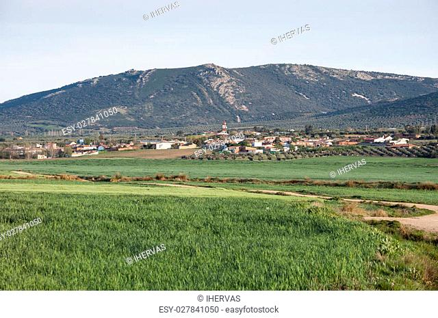 Small hamlet in an agricultural landscape in La Mancha, Ciudad Real Province, Spain. In the background can be seen the Toledo Mountains