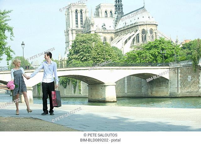 Caucasian couple walking along city river near Notre Dame