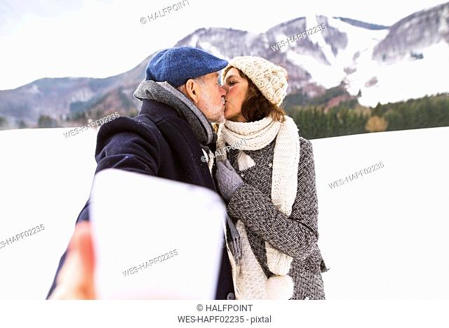 Senior couple kissing in winter landscape while taking selfie with cell phone