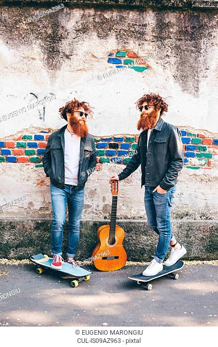Young male hipster twins with red hair and beards on sidewalk with skateboards