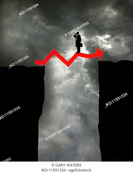 Businessman on top of arrow graph bridging the gap between two cliffs