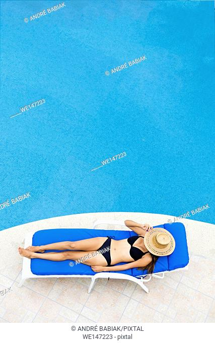 Young woman relaxing on lounger at swimming pool. View from above with negative space