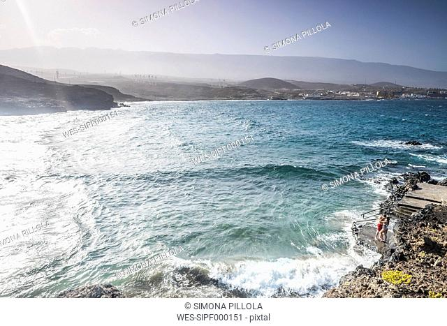 Spain, Tenerife, young couple in love kissing on a rock spur