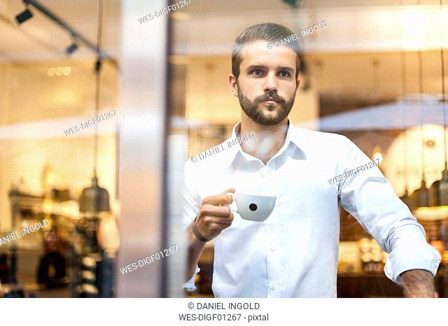 Businessman holding cup of coffee looking through window
