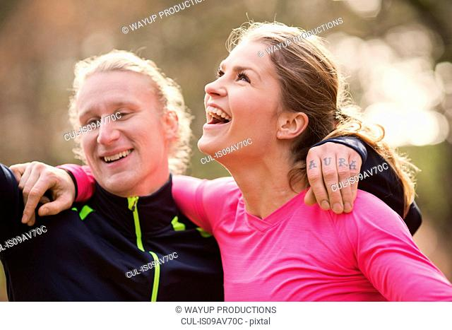 Head and shoulders of couple wearing sports clothing arms around each other looking away smiling