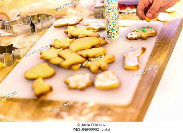 Girl's hand decorating Christmas cookies