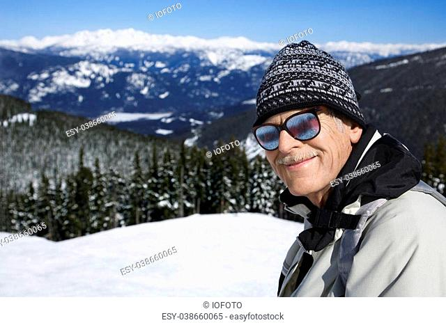 Caucasian senior man skier in goggles posing on mountain