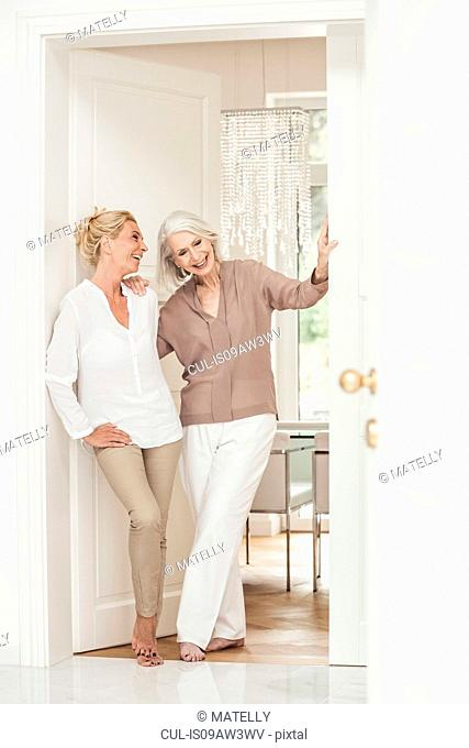 Mother and daughter standing together at home, laughing