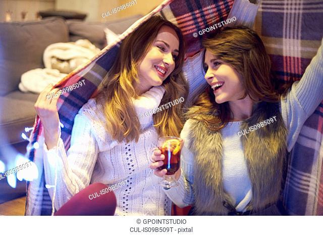 Friends enjoying mulled wine under blanket