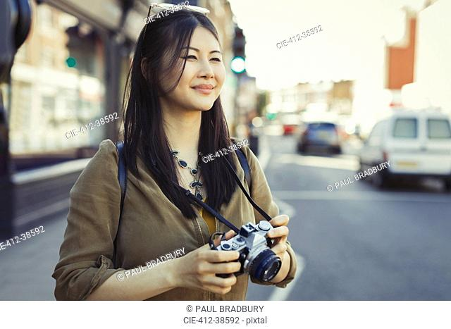 Smiling young female tourist photographing with camera on urban street