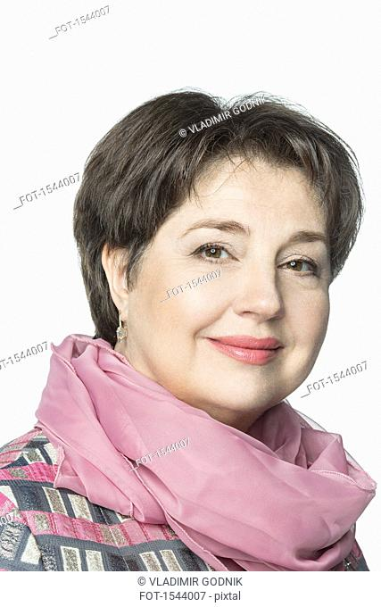 Close-up portrait of confident mature woman wearing scarf against white background
