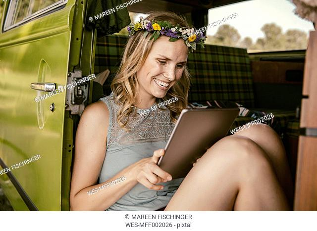 Happy young woman looking at tablet computer in van