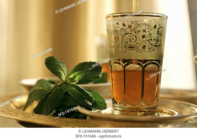 Peppermint tea in Middle Eastern glass & fresh mint leaves