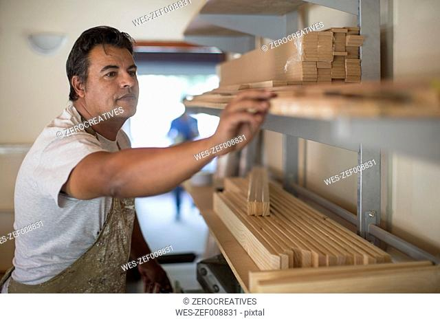 Man with wooden frames on shelf in canvas workshop