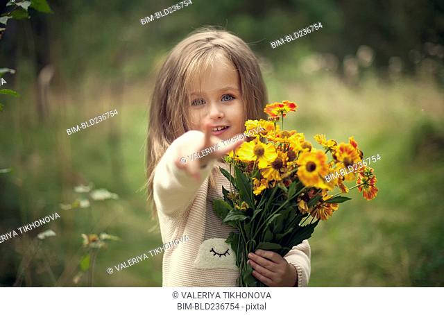 Smiling Caucasian girl pointing finger and holding flowers