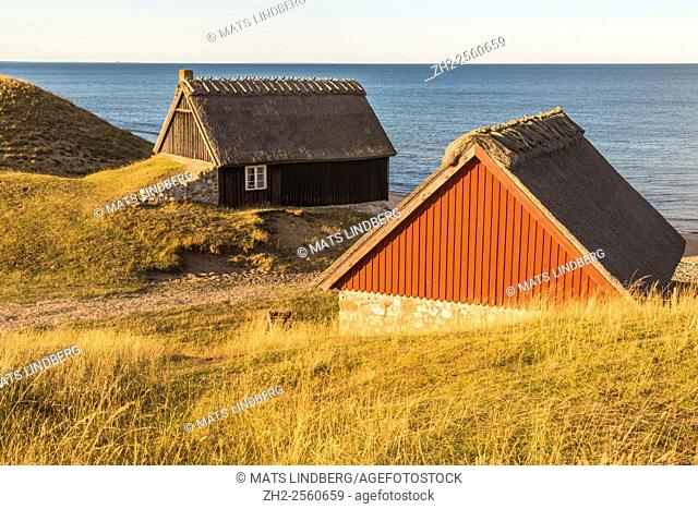 Coast of Haväng, Sweden, with two old houses at the shore, sunset light and horizon in the background