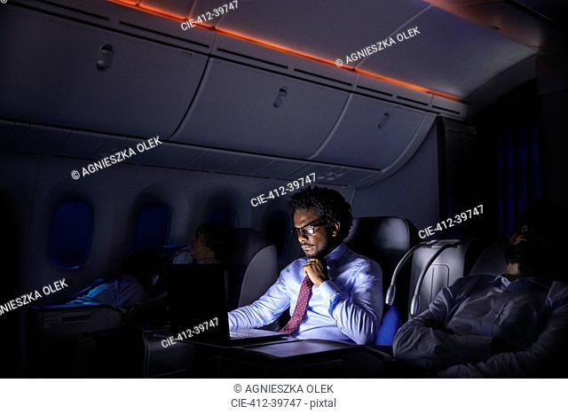 Businessman working at laptop on night airplane