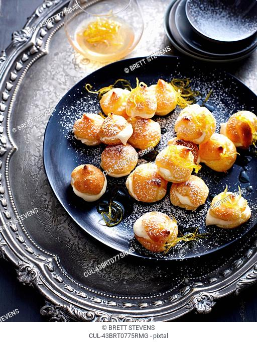 Plate of cream puffs with orange peel
