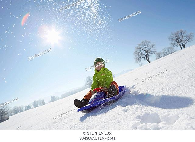 Young boy sitting on sled in snowy landscape