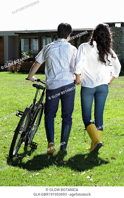 Rear view of a couple walking with a bicycle