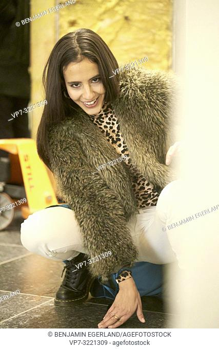 portrait of playful fashionable woman crouching on floor, in city, Munich, Germany