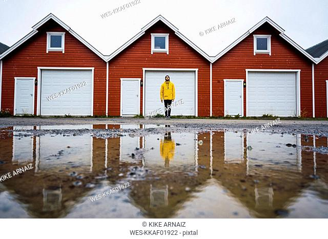 Norway, man standing in front of row of huts