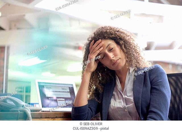 Exhausted young woman at desk in creative studio