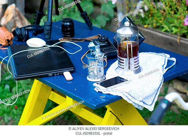 Camera equipment, laptop and cafetiere on table in garden