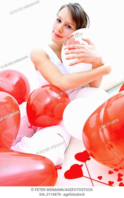 Young woman with heart and balloons, being in love (model-released)