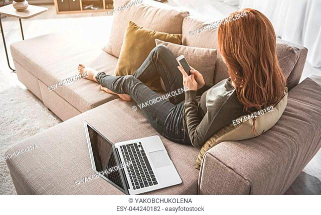 Red-haired girl resting on sofa with laptop near her. She is holding her mobile and enjoying relaxation in domestic atmosphere