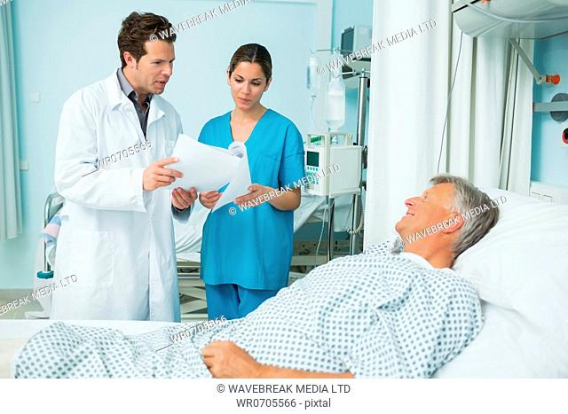 Doctor and female nurse holding a sheet of paper and talking to a male patient in a hospital