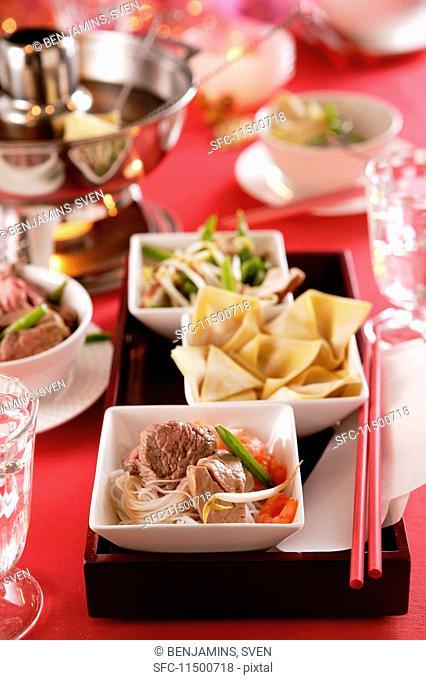 Pot au feu and bowls of various ingredients