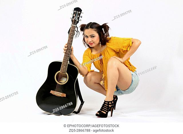 Girl with black guitar and high heels