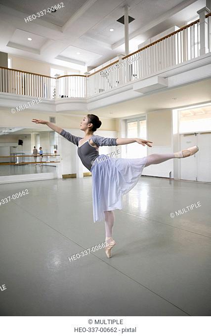 Graceful female ballet dancer practicing in dance studio