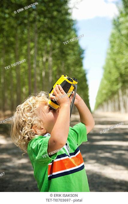 Boy 2-3 looking through binoculars