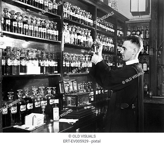 Man in a pharmacy mixing medicine All persons depicted are not longer living and no estate exists Supplier warranties that there will be no model release issues