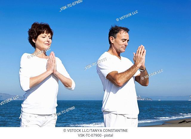 USA, California, San Francisco, Elder couple practicing yoga on beach